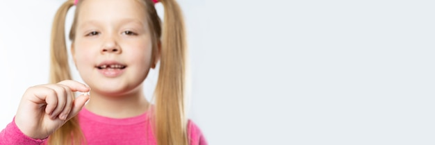 Kaukasische meisje met lang blond haar in roze kleren houdt een uitgetrokken melktand in haar handen op een lichte achtergrond. mondhygiëne concept