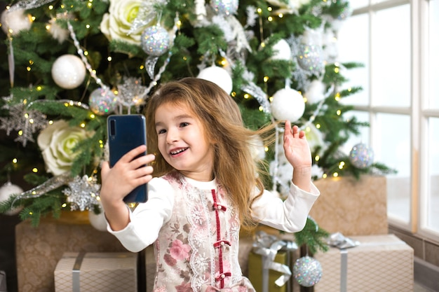 Kaukasische meisje op achtergrond van kerstboom neemt foto's van zichzelf met smartphone