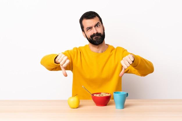 Kaukasische mens die ontbijt in een lijst heeft die duim met twee handen toont