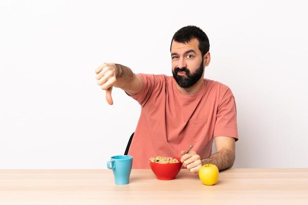 Kaukasische mens die ontbijt in een lijst heeft die duim neer met negatieve uitdrukking toont