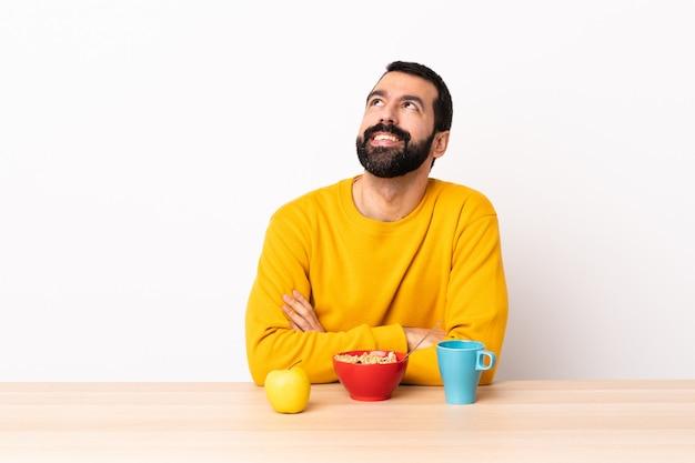 Kaukasische mens die ontbijt in een lijst heeft die een idee denkt terwijl omhoog het kijken