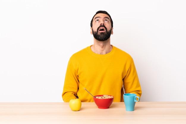 Kaukasische mens die ontbijt in een lijst heeft die omhooggaand en met verraste uitdrukking kijkt