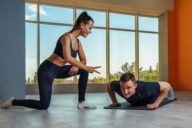 Kaukasische mens die opdrukoefeningen met persoonlijke trainer in geschiktheidsstudio maakt.