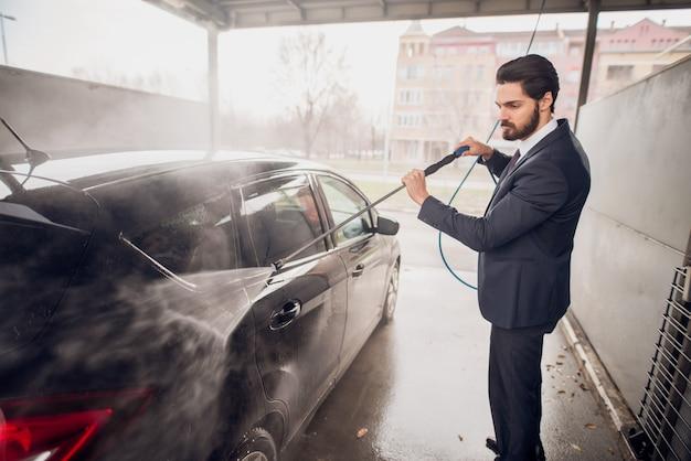 Kaukasische mens die zijn auto in autowasserette wast.