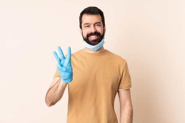 Kaukasische mens met baard die met een masker en handschoenen over muur gelukkig beschermt en drie met vingers telt
