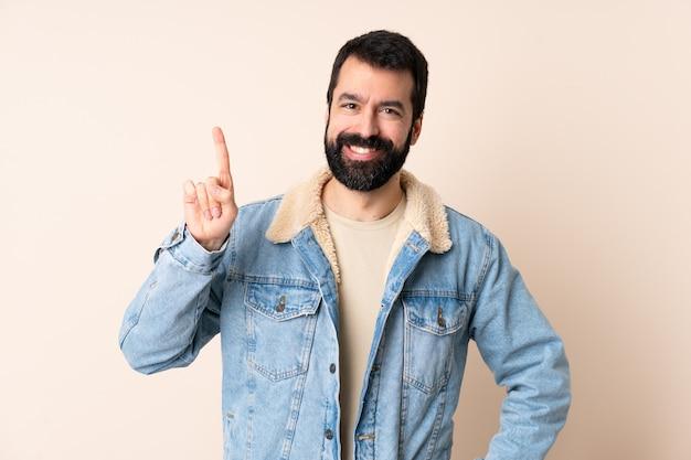 Kaukasische mens met baard over geïsoleerde ruimte die en een vinger in teken van het beste toont opheft