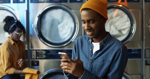 Kaukasische modieuze mens in gele hoed die en bericht op smartphone tikken texting terwijl het zitten in de ruimte van de wasserijdienst. knappe mens die op telefoon met glimlach typen en op te wassen kleren wachten.
