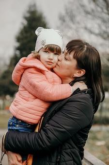 Kaukasische moeder die haar dochter in haar wapens houdt, en haar wangen kust. moeder dochter concept. moederdag concept.