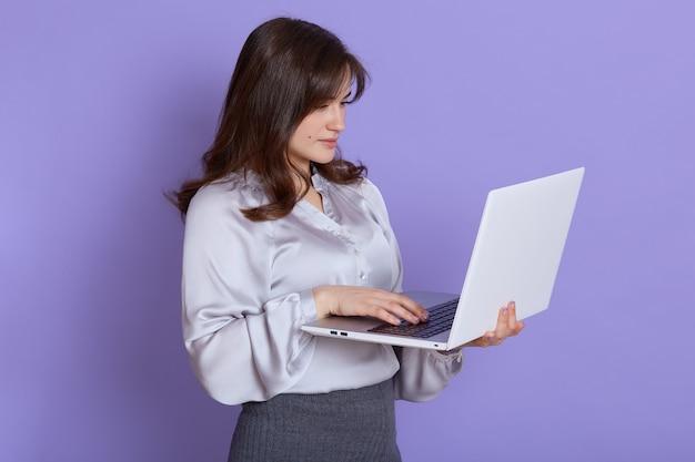 Kaukasische mooie jonge vrouw met laptop in handen poseren tegen lila muur, apparaatscherm kijken, geconcentreerd werken, elegante kleding dragen.
