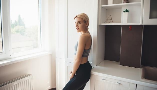 Kaukasische mooie vrouw die terugkijkt naar camera die thuis sportkleding draagt
