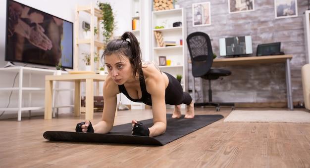 Kaukasische mooie vrouw die thuis planktraining doet en zwarte sportkleding draagt.