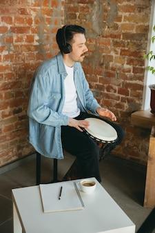 Kaukasische muzikant die handtrommel speelt tijdens online concert thuis geïsoleerd en in quarantaine geplaatst.