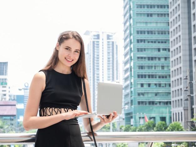 Kaukasische onderneemster die laptop computer met behulp van en glimlachend terwijl status bij voor modern bureau op het stadscentrum