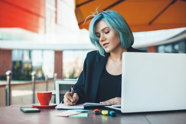 Kaukasische ondernemer met blauw haar die in een cafetaria aan de laptop werkt en wat aantekeningen maakt in een boek terwijl hij een kopje koffie drinkt