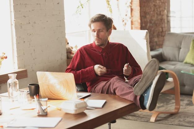 Kaukasische ondernemer zakenman manager die probeert te werken ziet er grappig lui uit en brengt tijd door