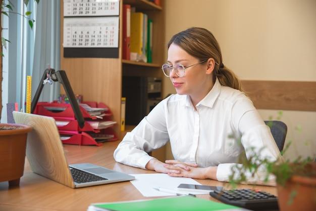 Kaukasische ondernemer, zakenvrouw, manager die geconcentreerd op kantoor werkt. ziet er serieus en druk uit, gekleed in klassieke kleding