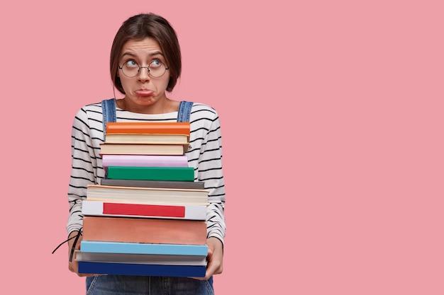 Kaukasische ontevreden jonge student houdt stapel boeken, bereidt zich voor op onderzoekssessie, portemonneert lippen in ontevredenheid