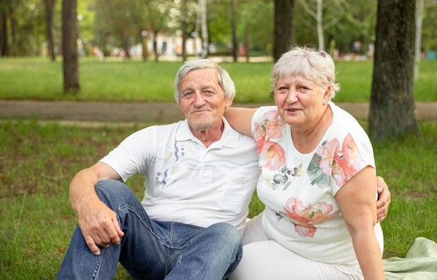 Kaukasische oudere stellen zitten en ontspannen in het park. hoger paar dat pret heeft en omhelst.
