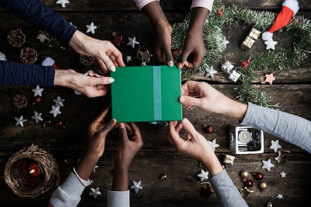 Kaukasische ouders met zwarte geadopteerde kinderen die allemaal samen de groene doos van de vakantiegift houden.
