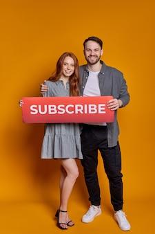 Kaukasische paar houden karton met abonnement inscriptie, dragen trendy modieuze kleding