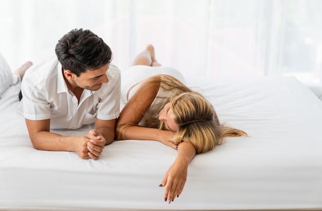 Kaukasische paarminnaar die op bed in vroege ochtend legt