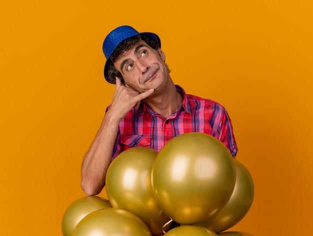 Kaukasische partijmens van middelbare leeftijd die partijhoed dragen die zich achter ballons bevinden die omhoog doen oproepgebaar op oranje achtergrond kijken