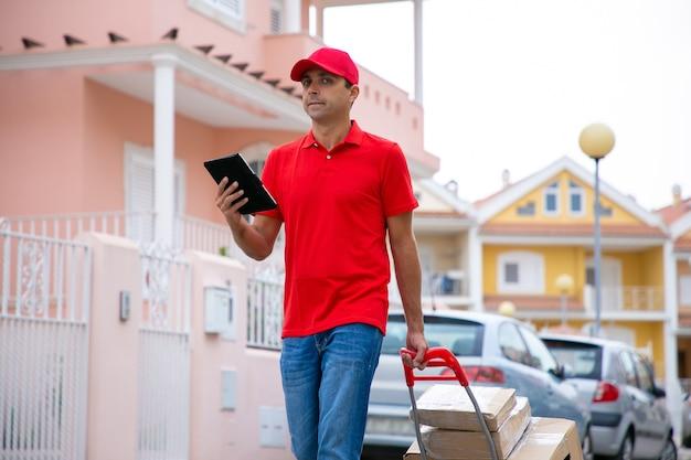 Kaukasische postbode met tablet en handvat van trolley met kartonnen dozen. zelfverzekerde bezorger in rood uniform doet zijn werk en bezorgt te voet de bestelling. bezorgservice en postconcept