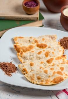Kaukasische qutab, kutab, gozleme geserveerd met sumakh, kruiden en yoghurt.