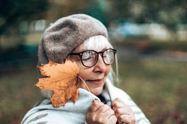 Kaukasische romantische vrouw in franse warme baret, glazen en wollen deken geniet in het park, de herfst