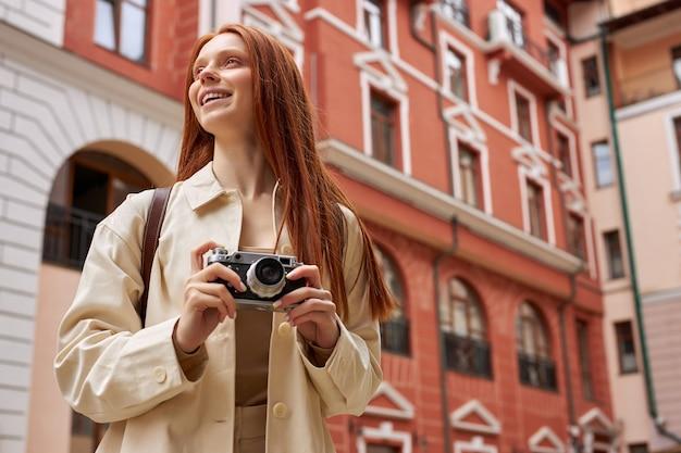 Kaukasische roodharige vrouwelijke toerist in beige jas staande op straat van de oude stad en fotograferen op camera...