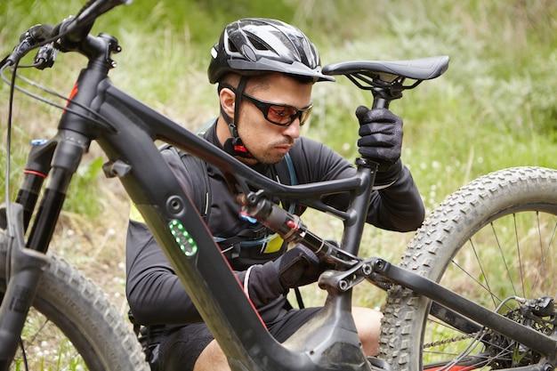 Kaukasische ruiter die beschermende kleding draagt die zetel van zijn fiets op batterijen aanpast
