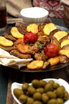 Kaukasische sac ichi met vlees en aardappelen geserveerd met groene olijven