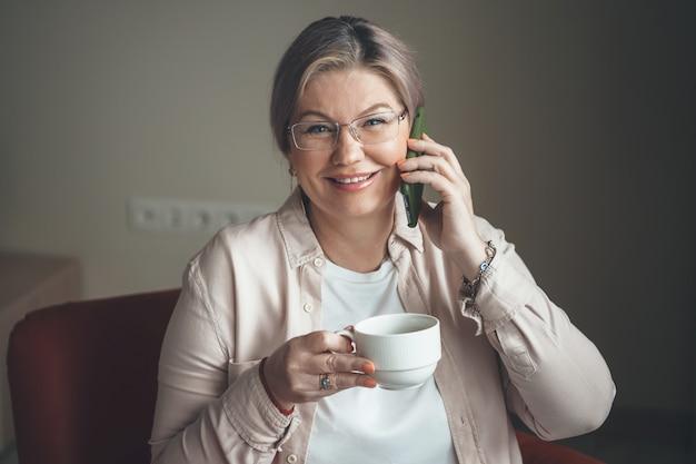 Kaukasische senior dame met bril met een kopje thee lacht tijdens het praten over de telefoon thuis