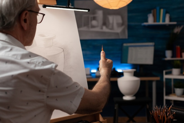 Kaukasische senior man die vaasontwerp op wit canvas trekt