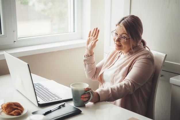 Kaukasische senior vrouw groet iemand op de laptop met een online vergadering terwijl u een kopje thee met croissant drinkt