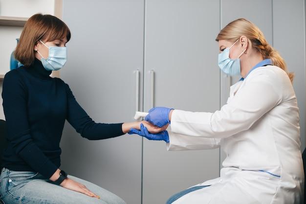 Kaukasische senior vrouw met blond haar meet de lichaamstemperatuur van de patiënt