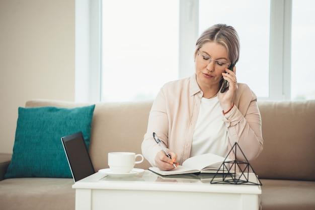Kaukasische senior vrouw praten over de telefoon tijdens het schrijven en werken op afstand op de computer thuis