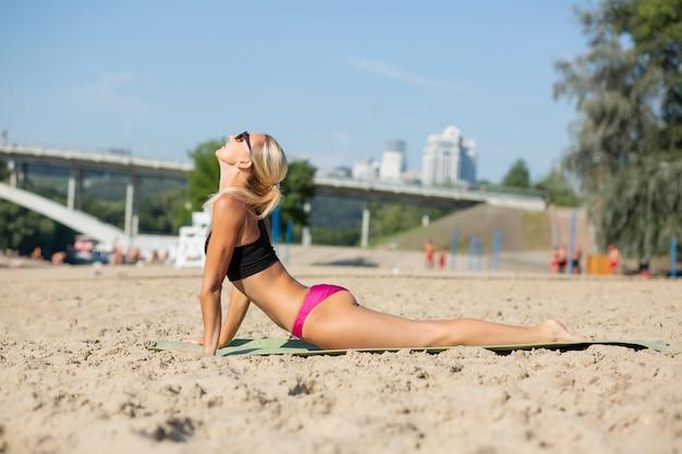 Kaukasische slanke blonde vrouw die yoga-oefeningen doet op het strand