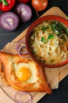 Kaukasische soep met noedels. lagman en khachapuri op houten tafelblad bekijken.