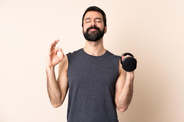 Kaukasische sportmens die met baard gewichtheffen over geïsoleerd maakt