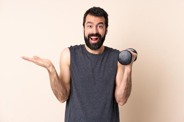 Kaukasische sportmens die met baard gewichtheffen over geïsoleerde muur met geschokte gelaatsuitdrukking maakt