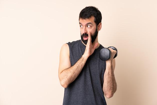 Kaukasische sportmens die met baard gewichtheffen over muur maakt die iets met verrassingsgebaar fluistert terwijl het kijken aan de kant