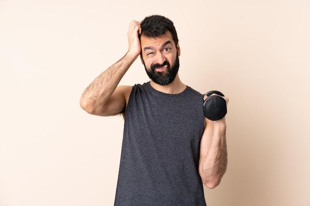 Kaukasische sportmens die met baard gewichtheffen over muur met een uitdrukking van frustratie en niet begrijpend maakt