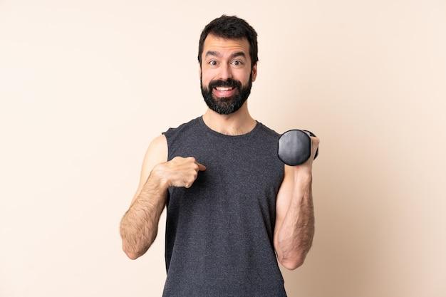 Kaukasische sportmens die met baard gewichtheffen over muur met verraste gelaatsuitdrukking maakt