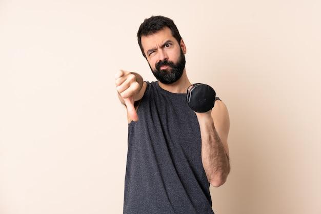 Kaukasische sportmens met baard die gewichtheffen maken die duim neer met twee handen tonen