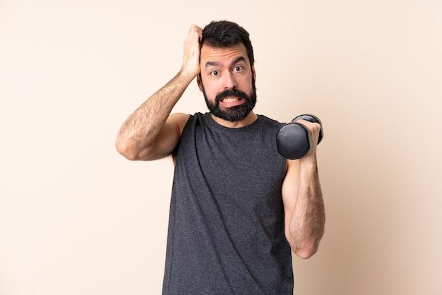 Kaukasische sportmens met baard die gewichtheffen over geïsoleerde muur maakt die zenuwachtig gebaar doet