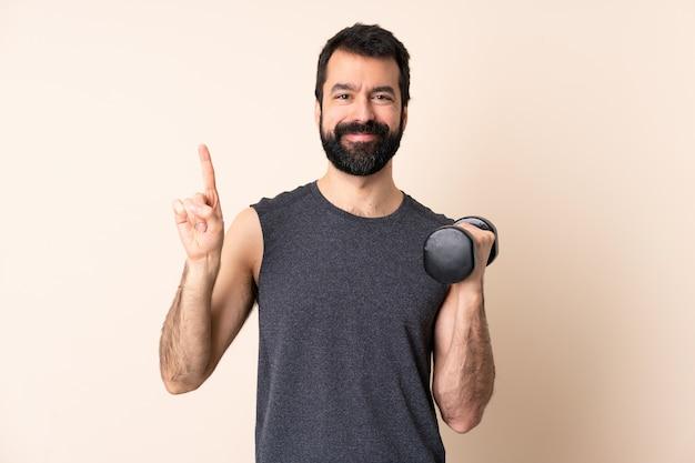Kaukasische sportmens met baard die gewichtheffen over geïsoleerde ruimte maakt die en een vinger in teken van het beste toont opheft