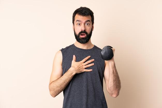 Kaukasische sportmens met baard die gewichtheffen over verraste en geschokte muur maken terwijl juist het kijken