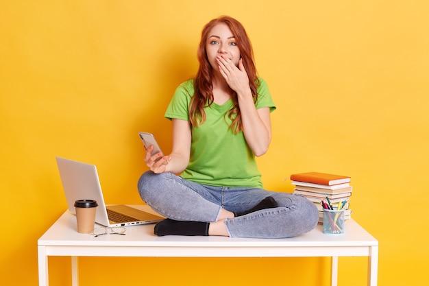 Kaukasische studentenvrouw die slimme telefoonzitting op bureau over geïsoleerde gele muur met behulp van