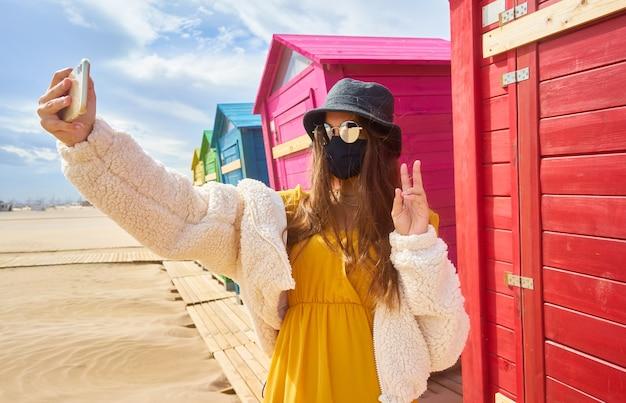 Kaukasische tiener die een selfie in een masker neemt
